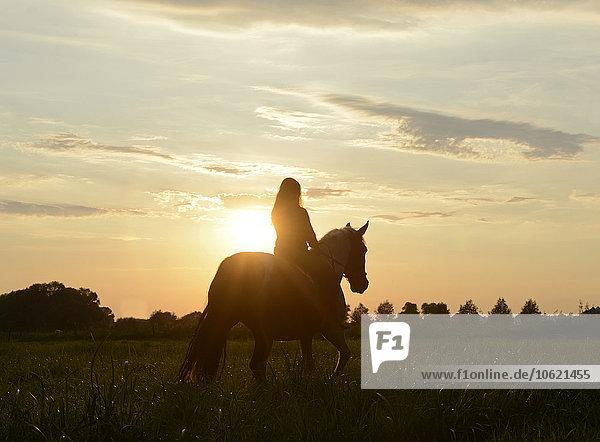 Junge Frau reitet in den Sonnenuntergang