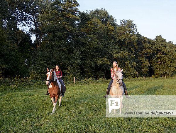 Zwei junge Frauen auf ihren Pferden