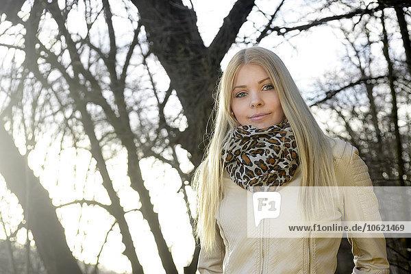 Porträt einer lächelnden blonden Frau in der Natur