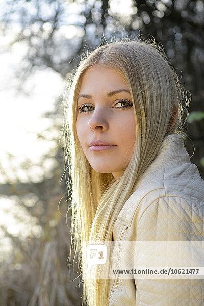 Porträt einer blonden jungen Frau in der Natur