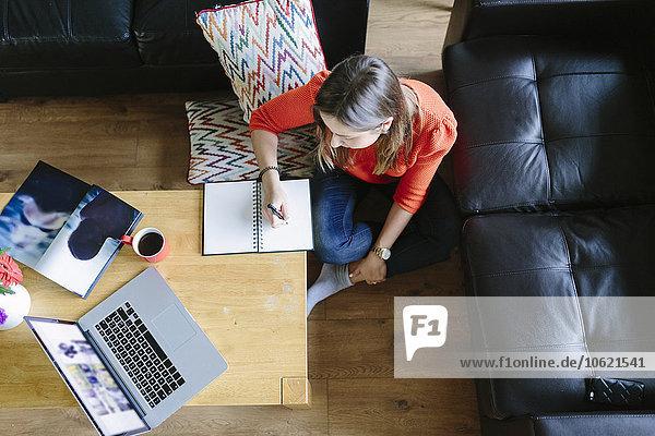 Junge Frau sitzt auf dem Boden in ihrem Wohnzimmer und schreibt etwas auf.