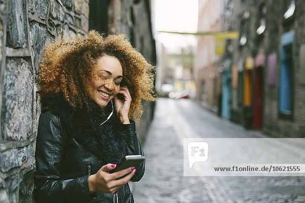 Irland  Dublin  lächelnde Frau mit Afro-Hörmusik mit Smartphone und Kopfhörer