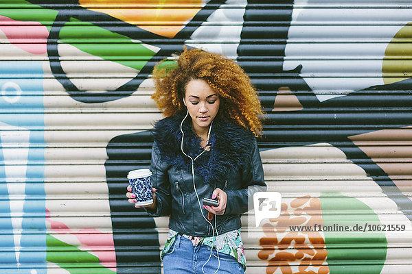 Frau mit Afro-Hörmusik mit Smartphone und Kopfhörer