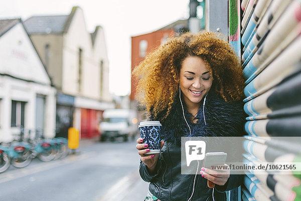 Irland  Dublin  lächelnde Frau mit Kaffee zum Musikhören mit Smartphone und Kopfhörer