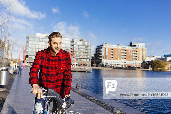 Irland  Dublin  junger Mann am City Dock mit City Bike