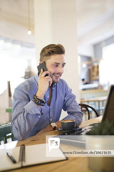 Mann mit Smartphone und Laptop in einem Coffee-Shop