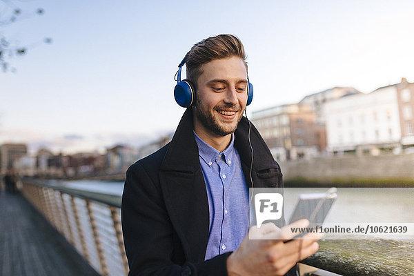Irland  Dublin  junger Mann mit Smartphone  der Musik mit Kopfhörern hört.