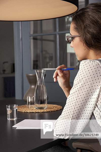 Junge Frau sitzt am Tisch und schreibt auf Papier.