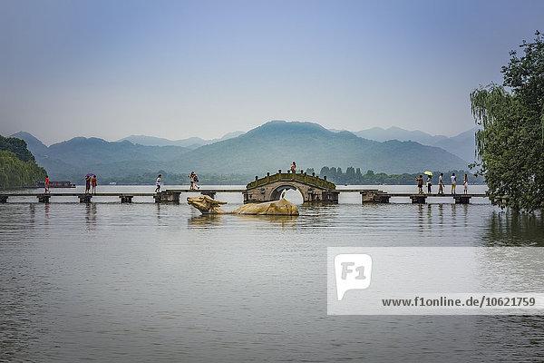 China  Zhejiang  Hangzhou  Riesige goldene Wasserbüffel und Fußgänger auf einer Brücke am Westsee