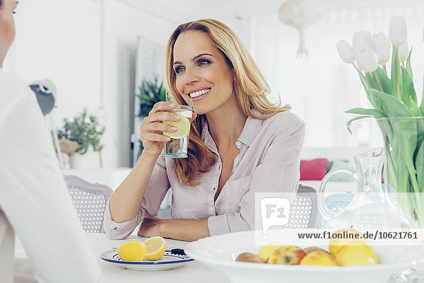 Portrait of smiling blond woman sitting at dining table communicating with her female friend