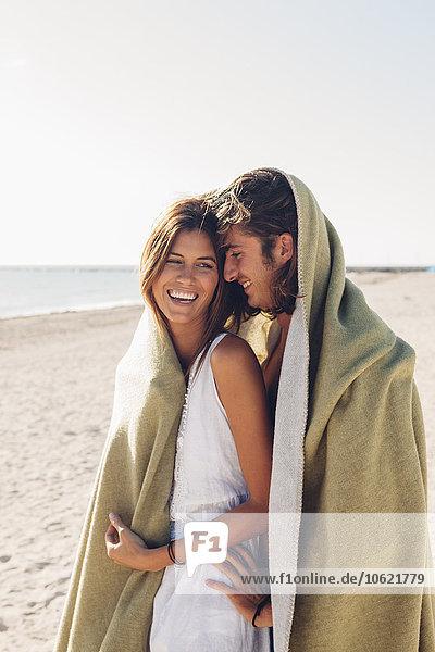 Romantisches junges Paar am Strand in eine Decke gehüllt