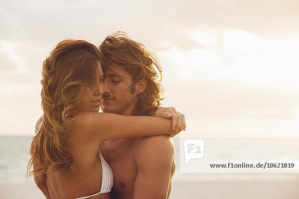 Romantisches  junges Paar  das sich am Strand umarmt.