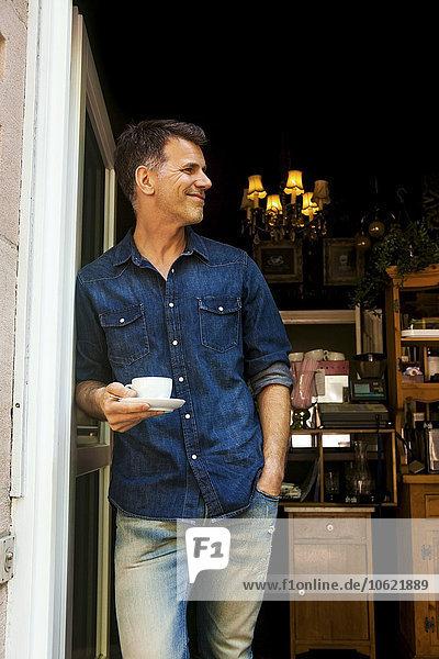 Reifer Mann  der sich in die Tür des Cafés lehnt und eine Tasse Kaffee hält.