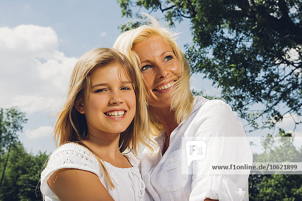 Portrait of happy teenage girl with her mother in a park