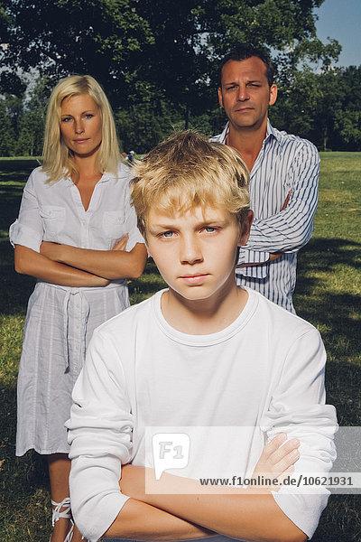 Bildnis eines Jungen mit verschränkten Armen und seinen Eltern im Hintergrund