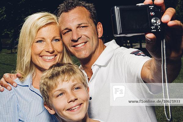 Glückliche Familie beim Fotografieren mit einer Digitalkamera