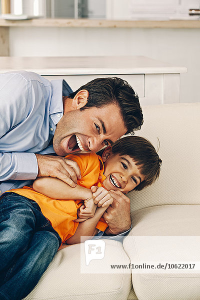 Playful father and son on sofa