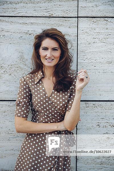 Porträt einer lächelnden brünetten Frau im Freien