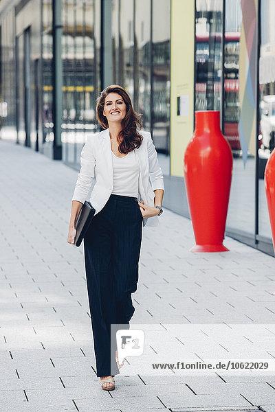 Lächelnde Geschäftsfrau auf dem Bürgersteig