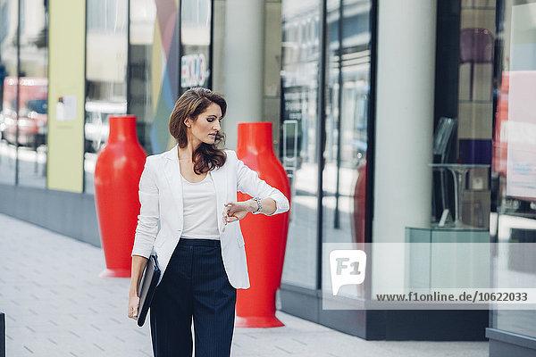 Geschäftsfrau im Freien  die die Zeit überprüft.