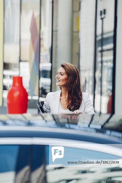 Lächelnde Geschäftsfrau im Freien hinter dem Auto