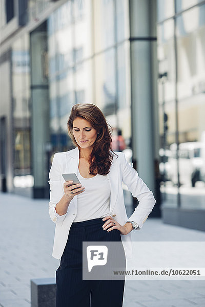 Businesswoman outdoors looking on cell phone