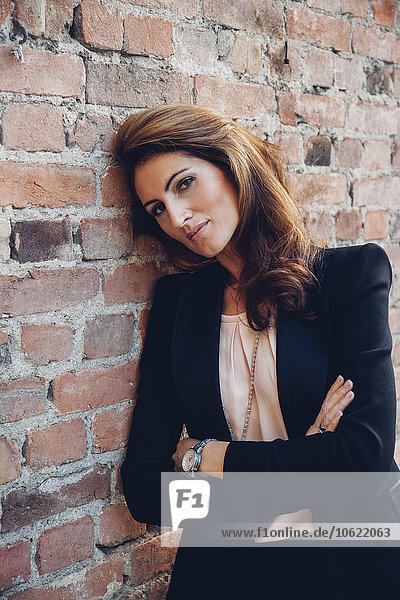 Portrait of smiling businesswoman leaning against brick wall