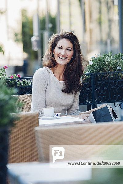 Glückliche Frau mit Einkaufstasche im Outdoor-Café