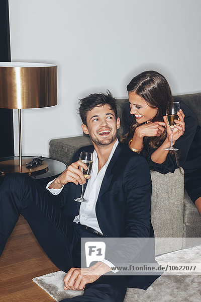Happy young couple with glasses of champagne at sofa
