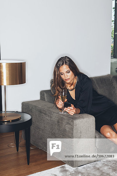 Young woman with glass of champagne looking on cell phone