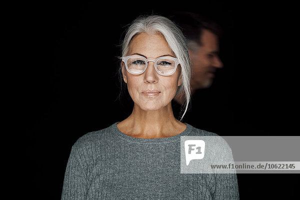 Porträt einer grinsenden Frau mit Brille vor schwarzem Hintergrund