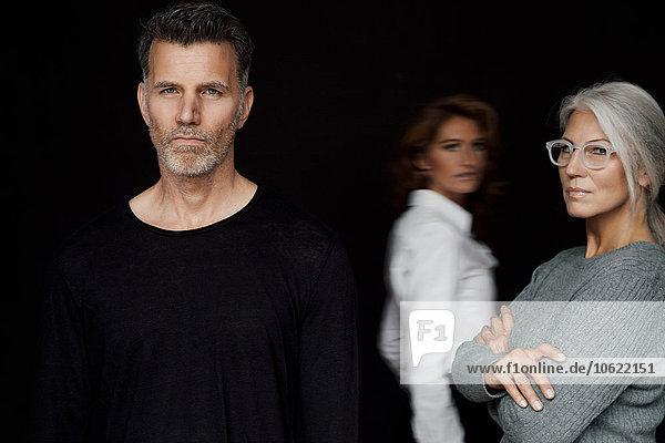 Porträt seriös aussehender Geschäftsleute vor schwarzem Hintergrund