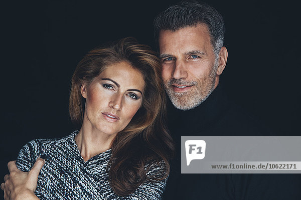 Portrait of couple in front of black background