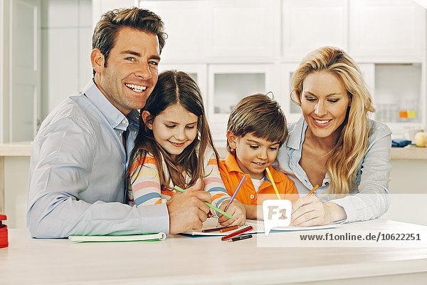 Glückliche vierköpfige Familie am Tisch mit Malbuch
