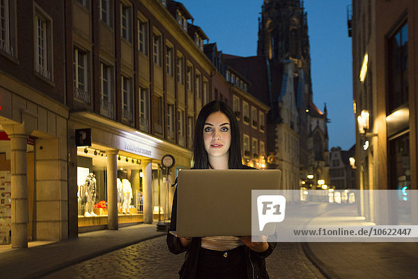 Germany  Muenster  portrait of young woman with laptop in the city at evening