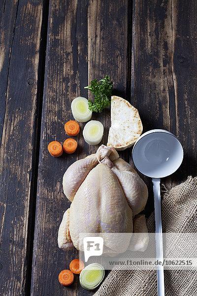 Rohes Hühnerfleisch  Gemüse und Suppenlöffel auf dunklem Holz