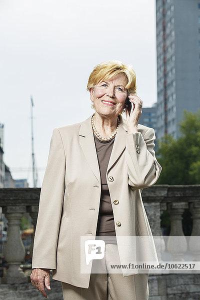 Deutschland  Berlin  Porträt einer lächelnden Senior-Geschäftsfrau beim Telefonieren mit dem Smartphone