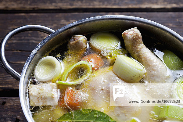 Kochtopf mit rohem Hühnerfleisch  Zwiebeln  Kräutern und Gemüse  Nahaufnahme