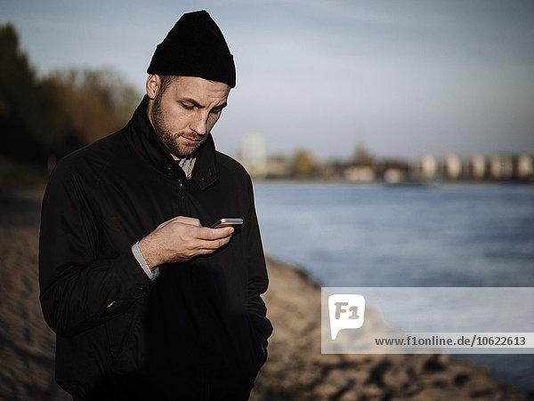 Deutschland  Köln  Mann am Rhein mit seinem Smartphone