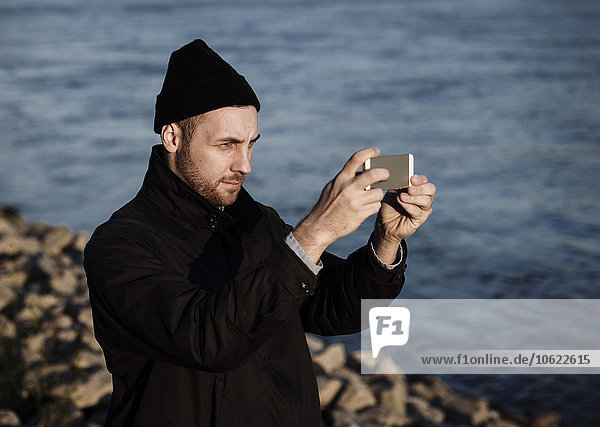 Deutschland  Köln  Mann in Herbstmode vor dem Rhein stehend mit einem Selfie