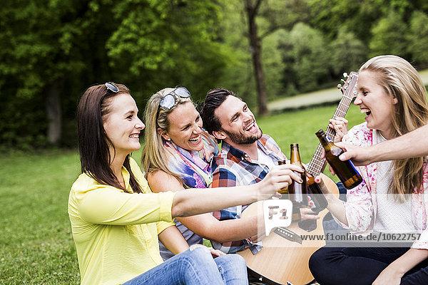 Glückliche Freunde klirren Bierflaschen im Park