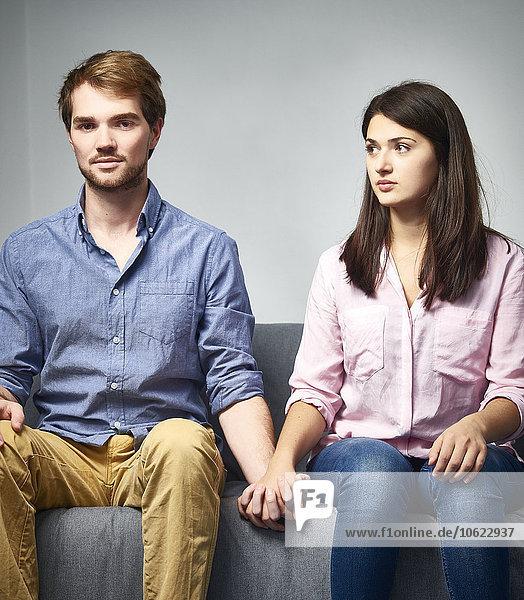 Seriöses junges Paar  das auf der Couch sitzt und Händchen hält.