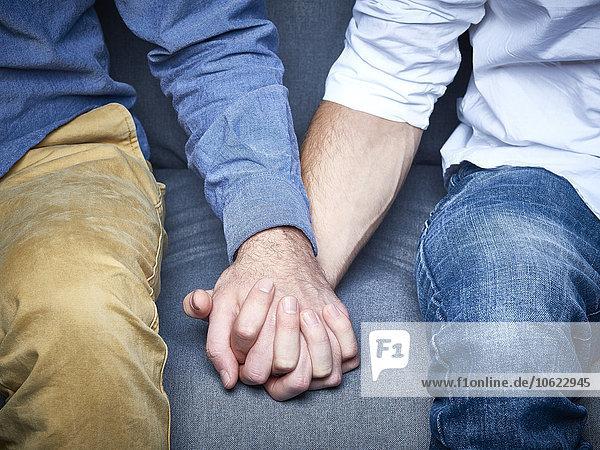 Teilansicht eines schwulen Paares  das sich an der Hand hält.