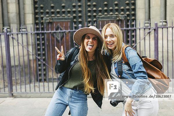 Spanien  Barcelona  zwei verspielte junge Frauen vor dem Eingangsportal