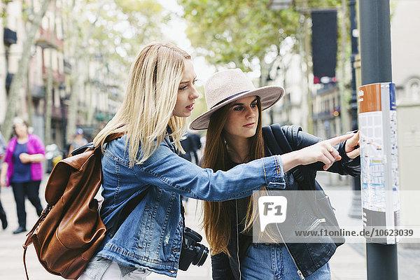 Spanien  Barcelona  zwei junge Frauen beim Blick auf den Stadtplan am Pol