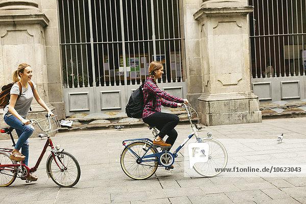 Spanien  Barcelona  zwei junge Frauen auf dem Fahrrad in der Stadt