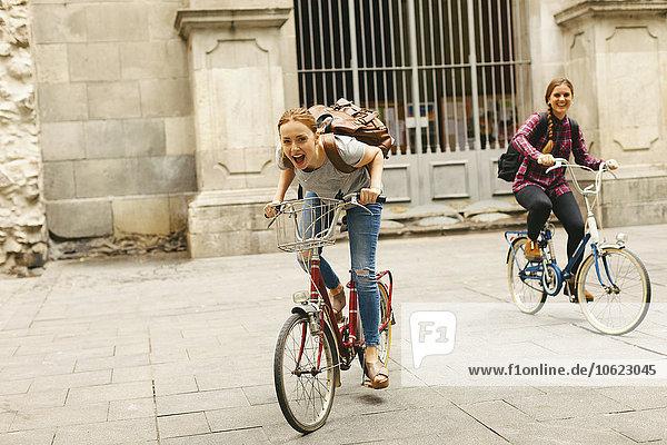 Spanien  Barcelona  zwei glückliche junge Frauen beim Radfahren in der Stadt