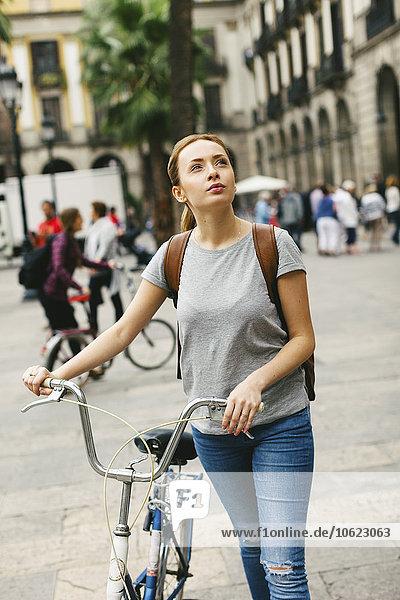 Spanien  Barcelona  junge Frau beim Fahrradfahren in der Stadt