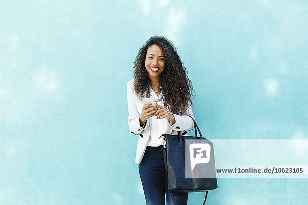 Portrait of smiling young businesswoman with smartphone and leather bag in front of a blue wall