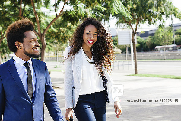 Spanien  Barcelona  Porträt von zwei lächelnden jungen Geschäftsleuten  die Seite an Seite gehen